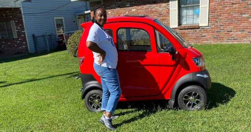 Woman shows of her tiny red car