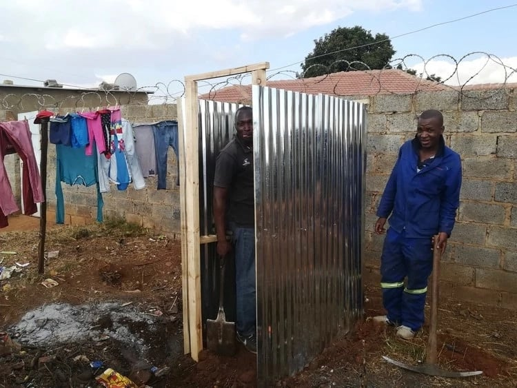 Some of the residents pictured constructing one of the toilets. Source: GroundUp/Zoë Postman