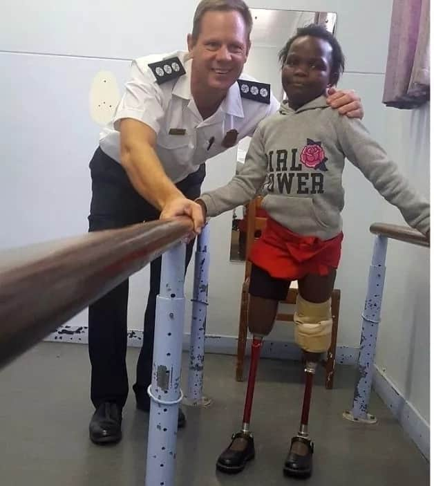 Nelson Mandela Bay Fireman, Alton Senekal, with 7-year-old double amputee, Siphosethu Ncandana as she tries out her prosthetic legs and shoes