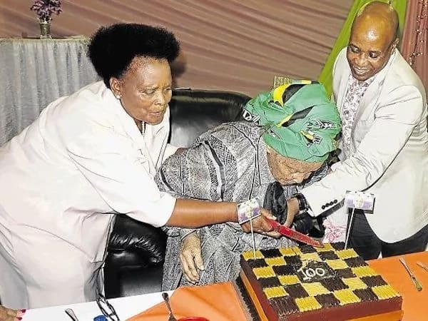 Gija's daughter and Premier Masualle help her cut the cake. Source: Daily Dispatch