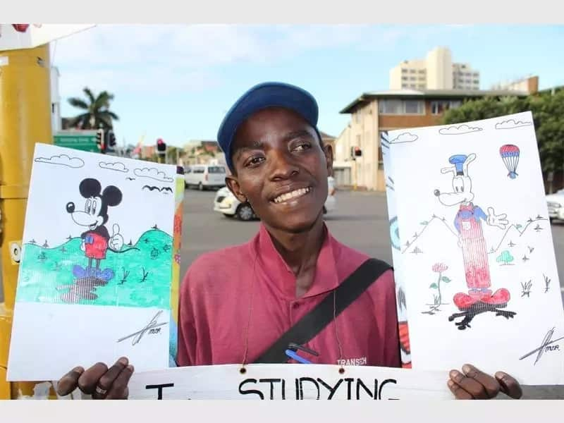 Musa Goba displays some of his drawings while appealing for help at a street corner. Source: Berea Mail