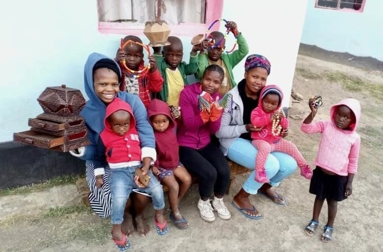 Nomtha (seated right) with the abandoned children she cares for. Source: GroundUp