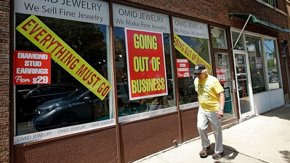 A man in front of a retail shop that is going out of business. Photo source: ABC News