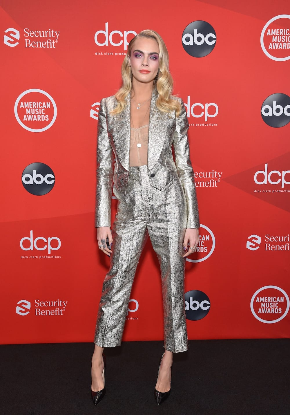 Cara Delevingne poses in a shimmering duo-chrome suit.